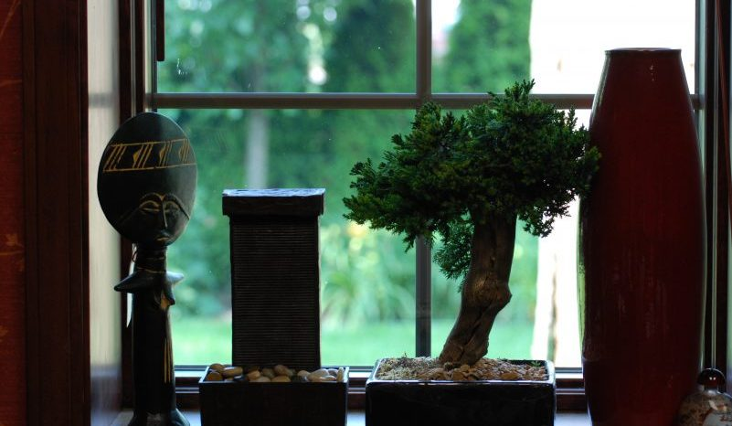 little tree, a vase, and two sculptures in a window sill