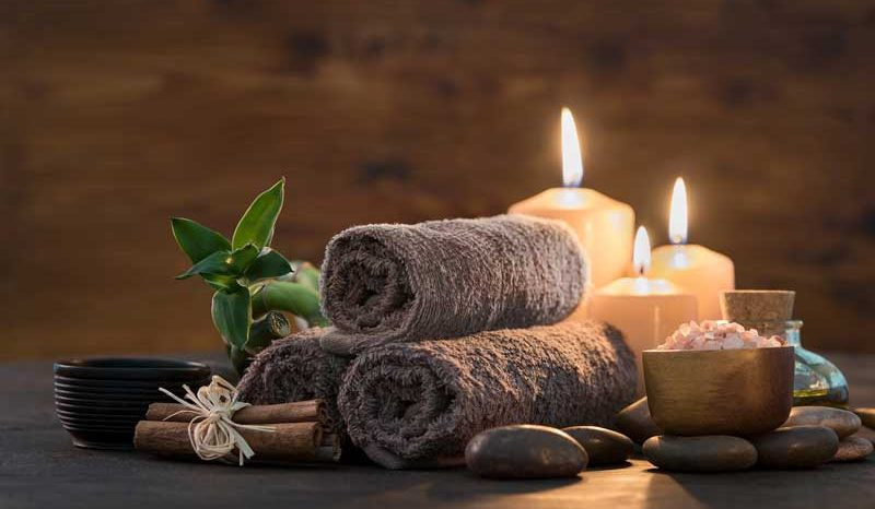 rolled up towels next to smooth stones and bowl full of flowers and three lit candles